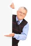 Monsieur posant derrière un panneau blanc et faire des gestes Photographie stock libre de droits