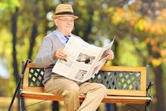 Monsieur supérieur assis sur un banc lisant un newspaperoutdoor Image libre de droits