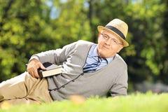 Monsieur supérieur avec le chapeau se trouvant sur une herbe avec un livre en parc Photo libre de droits