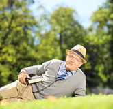 Monsieur supérieur avec le chapeau se trouvant sur une herbe avec un livre en parc Photos stock
