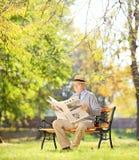 Monsieur supérieur avec le chapeau sur le banc et lire un journal dans a Image stock