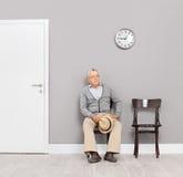 Monsieur supérieur ennuyé s'asseyant dans un lobby de bureau Photo stock