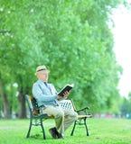 Monsieur supérieur lisant un livre en parc Photos libres de droits