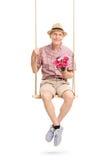 Monsieur supérieur s'asseyant sur l'oscillation et tenant des fleurs Photo stock