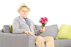 Monsieur supérieur s'asseyant sur un sofa et tenant des fleurs Images stock