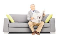 Monsieur supérieur s'asseyant sur un sofa moderne avec le journal Photographie stock libre de droits