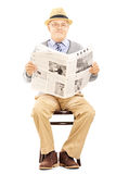 Monsieur supérieur sur une chaise en bois tenant un journal photos stock