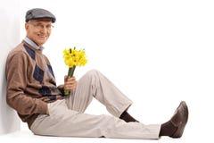 Monsieur supérieur tenant des fleurs Photo libre de droits