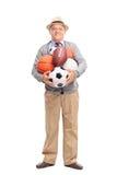 Monsieur supérieur tenant un groupe de boules de sports Photos libres de droits