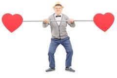 Monsieur supérieur tenant un tuyau avec des coeurs sur les deux extrémités Images libres de droits