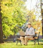 Monsieur supérieur travaillant sur l'ordinateur portable posé sur le banc en parc Photos libres de droits