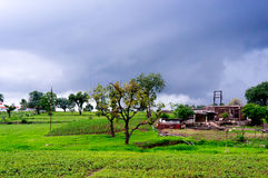 Monsoon clouds over fields and a storage shed Stock Photos