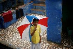 Monsoon in India,blue city Jodhpur. Small girl holding broken umbrella standing on a roof during monsoon rains in Jodhpur, India Stock Photo