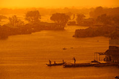 Monsoon rain as the sun sets on Tonle Sap Lake, Cambodia Royalty Free Stock Photo
