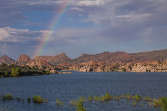 Monsoon Rainbow Over Watson Lake. A rainbow sits over Watson Lake Prescott Arizona during the monsoon Royalty Free Stock Photography