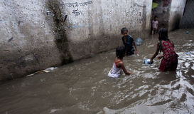 Monsoon at slum. Slums of lower part of Dhaka city get flooded after every heavy rainfall. Water enters into their houses. The photo was taken at early morning Stock Photos