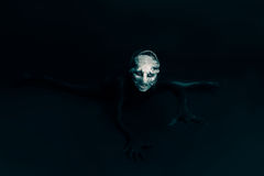 Monster or alien crawls toward you on black background Stock Photo