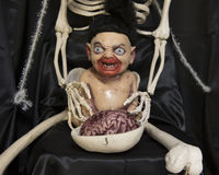 Monster baby with bloody mouth in skeleton`s lap Stock Photography