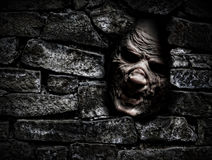 Monster behind the wall. Horror monster looking out from hole in the wall Stock Image