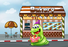 A monster with a cake near the bakery Royalty Free Stock Photos