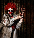 Monster clown checking the pulse on a severed hand Stock Images