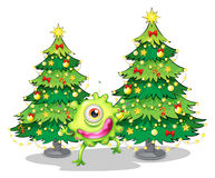 A monster dancing in front of the christmas trees Stock Photography