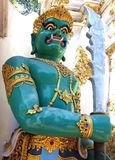 Monster Deity Guarding a Wat in Chiang Mai. A statue of a crowned green man beast warrior with large fangs holding a large sword and covered in golden jewelry royalty free stock image