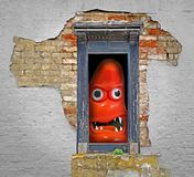 Monster at the door in derelict eerie haunted house. Photo of a googly eyed monster baring its teeth at the door of a derelict haunted house stock photos
