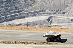 Monster dump truck in open pit mine. A monster dump truck carries 250 tons of rock out of an open pit mine stock photo