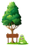 A monster beside the empty wooden signboard under the tree Royalty Free Stock Image