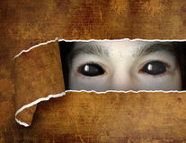 Monster eye in hole in the paper. Dark series - a look from darkness. Monster eye in hole in the paper Stock Image