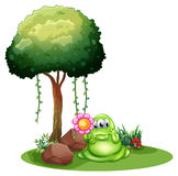 A monster holding a flower standing near the tree Royalty Free Stock Image