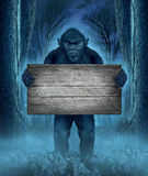 Monster Holding  A Sign. Monster holding a rustic blank old wood sign as a creepy halloween concept with a werewolf lurking as a bigfoot creature coming out of a Stock Image