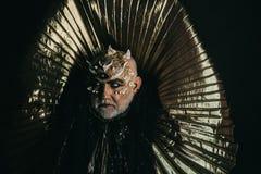 Monster met scherpe doornen en wratten, fantasie en verschrikkingsconcept Mens met draakhuid en gebaard die gezicht op zwarte wor stock foto