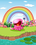 A monster at the pond with a rainbow in the sky Stock Photo