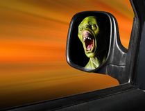 Monster in rear view mirror. Rear view mirror reflecting fearful monster face - road safety metaphor Stock Photo