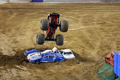 Monster truck flying in air. A monster truck flies over smashed cars at Qualcomm Stadium in San Diego during a show that took place on 1/19/09 Stock Image