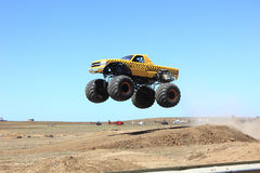 Monster truck. Yellow monster truck jumping over sand dune jump at public arena.....FT Royalty Free Stock Photo