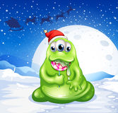 A monster wearing Santa's hat while eating a lollipop Stock Images