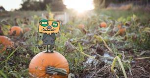 Monsterkarikatur, die auf Halloween-Kürbis steht Lizenzfreie Stockfotografie