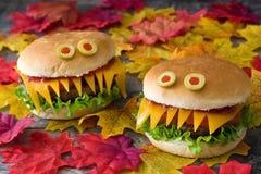 Monstres d'hamburger de Halloween sur des feuilles d'automne Photos libres de droits