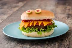 Monstres d'hamburger de Halloween sur le bois Image stock