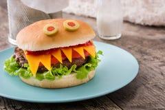 Monstres d'hamburger de Halloween sur le bois Photographie stock