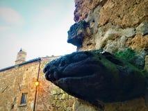 Monstruo, arquitectura, máscara grotesca y cuento en Civita di Bagnoregio, ciudad en la provincia de Viterbo, Italia imágenes de archivo libres de regalías