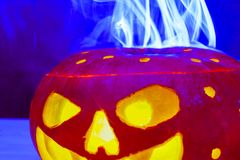 Monstruo de la calabaza de Halloween de la luz de neón que emite humo azul foto de archivo
