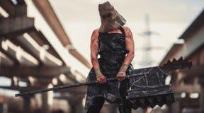 Monstruo del mutante con el arma en la forma de martillo, de sierra y de un hacha Ima Fotos de archivo libres de regalías