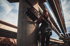 Monstruo del mutante con el arma en la forma de martillo, de sierra y de un hacha Ima imágenes de archivo libres de regalías