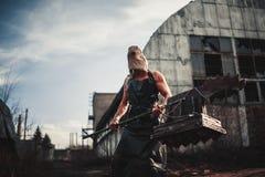 Monstruo del mutante con el arma en la forma de martillo, de sierra y de un hacha Ima Fotografía de archivo libre de regalías