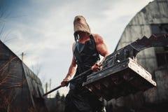 Monstruo del mutante con el arma en la forma de martillo, de sierra y de un hacha Ima foto de archivo libre de regalías