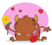 Monstruo marrón feliz que sostiene una flor amarilla Imágenes de archivo libres de regalías